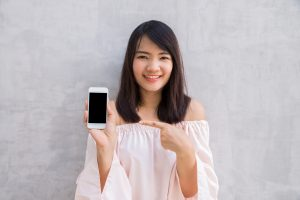 Smiling woman showing a blank smartphone screen standing on conc