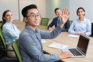 Smiling businessman raising hand at conference